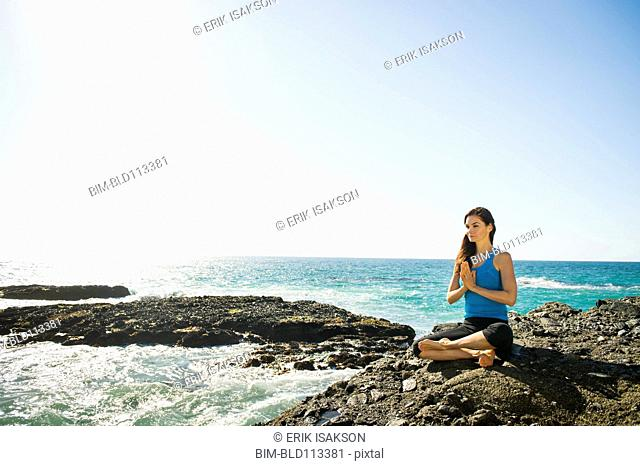 Mixed race woman meditating on rocky beach