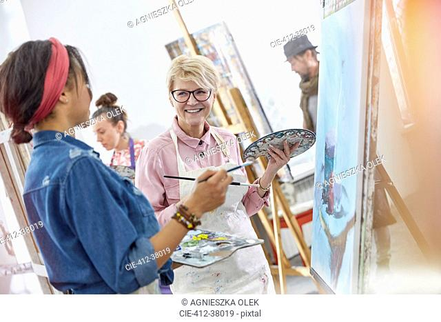 Smiling female artists with paintbrushes and palettes painting in art class studio