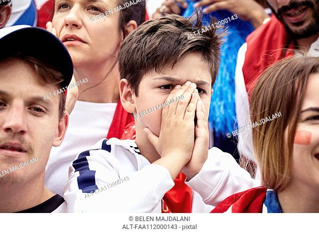 Young football fan covering face during football match