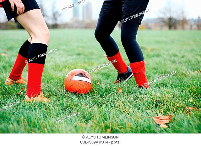 Legs of female soccer players practicing in park