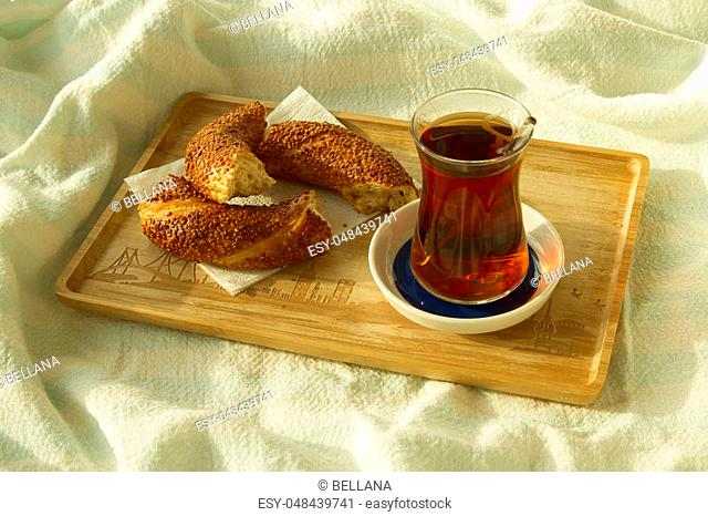 Morning tea, Bagel and cup of turkish tea on the wood tray with Istanbul picture on the bedcover