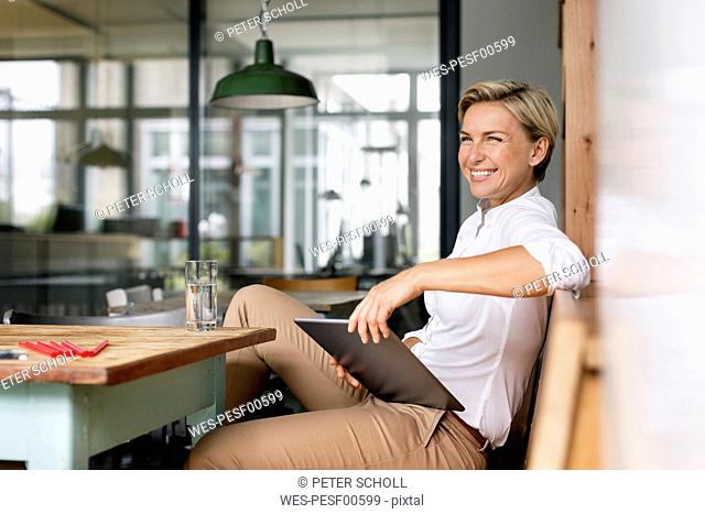 Happy blond woman with tablet sitting at table