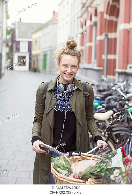 Portrait enthusiastic young woman with headphones riding bicycle on city street