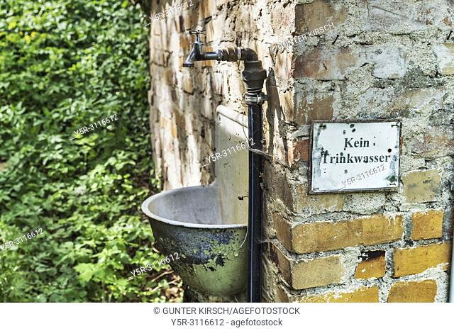 """A water tap and a sink are attached to the outside of an old building. Next to it is a sign """"""""No drinking water"""""""". Glashuette, city Baruth / Mark"""