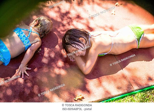 Two girls lying on blanket wearing bikinis in sunlight