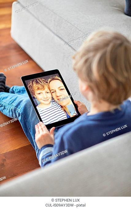 Boy sitting on floor talking to mother and brother on digital tablet video call
