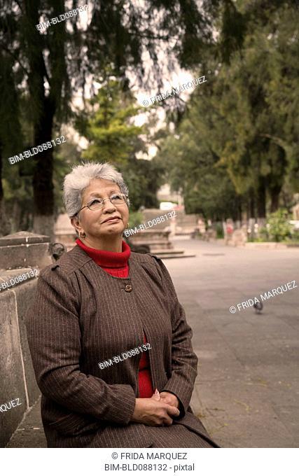 Senior Hispanic woman sitting in park