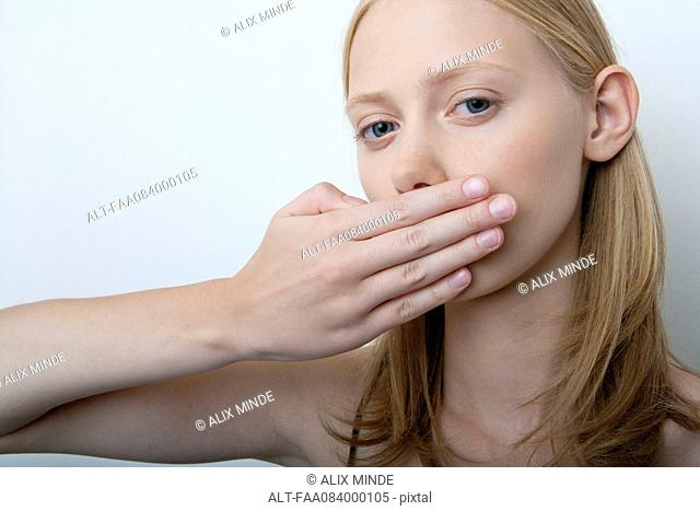 Young woman covering mouth with hand