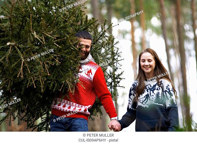Young couple carrying Christmas tree on shoulders in woods