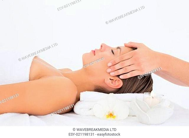 Attractive young woman receiving head massage at spa center