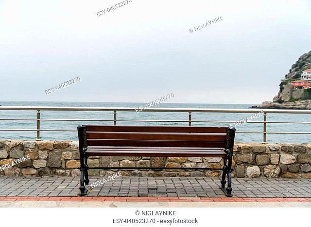 Empty wooden bench with viewpoint looking out to sea, cloudy weather