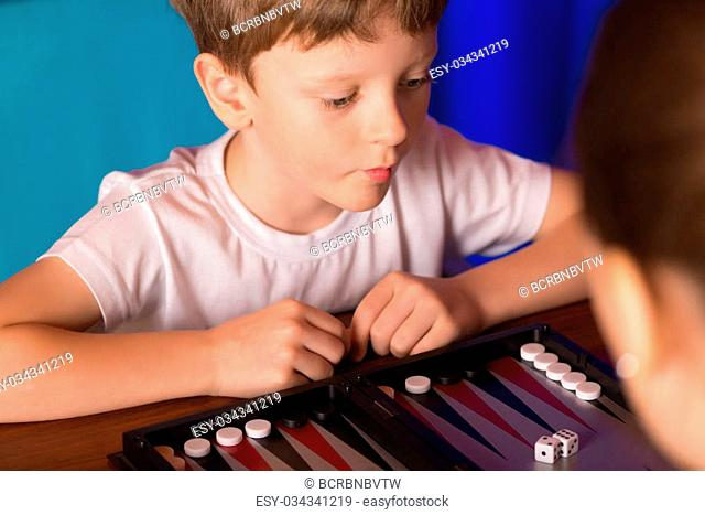 boy playing ancient Eastern game called Backgammon
