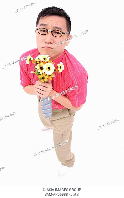 Man in shirt and tie holding flower bouquet, frowning