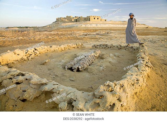 A Local Siwan Man Looks At A Shallow Grave Site Outside Siwa Town At The Siwa Oasis, Siwa Egypt