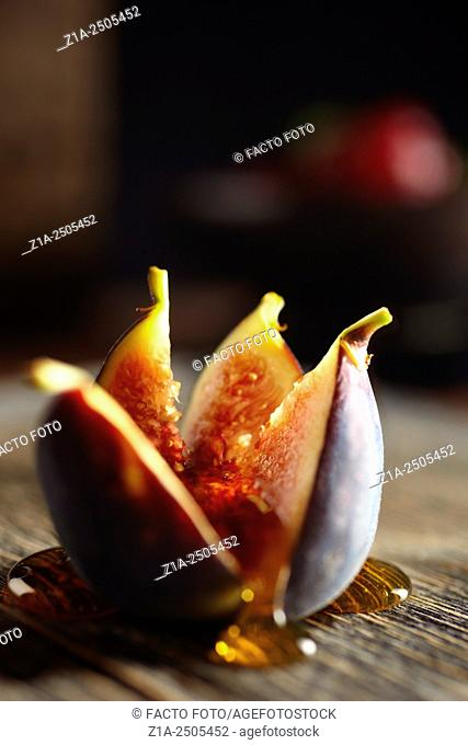 Fig cut in four pieces covered with honey on a dark background