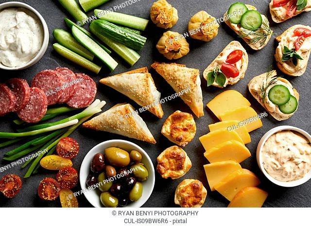 Appetiser snack spread with open sandwiches, olives and cheese , overhead view