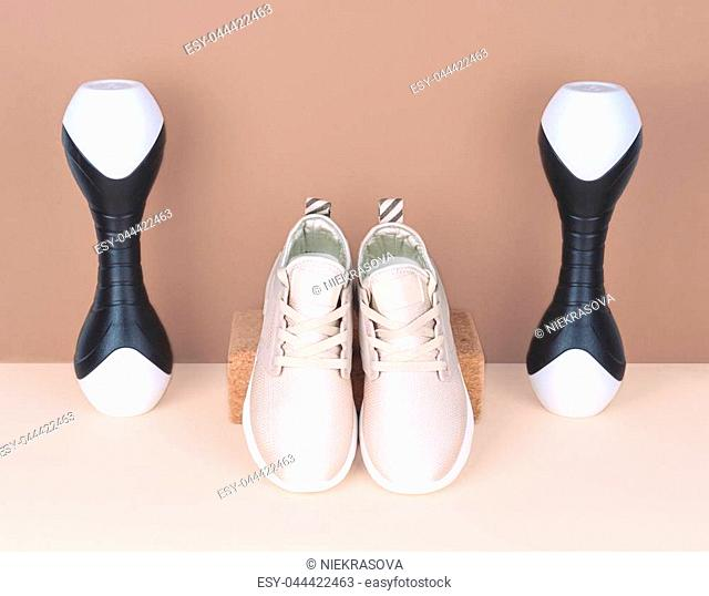 Shot of golden sneakers on beige background. Stylish healthy lifestyle concept