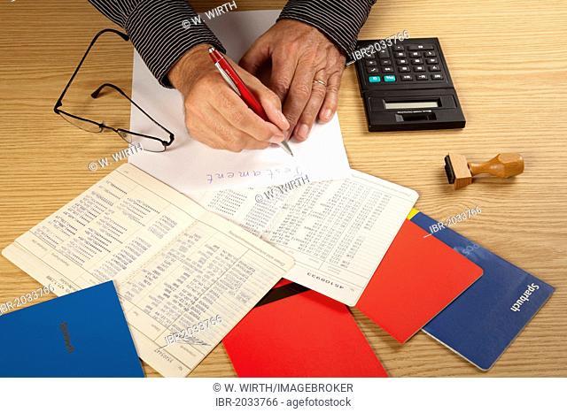 Hands of a senior writing a testament, bankbooks