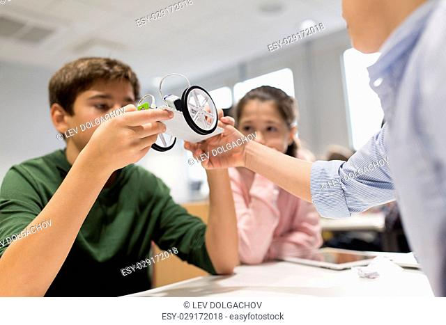 education, children, technology, science and people concept - group of happy kids building robots at robotics school lesson