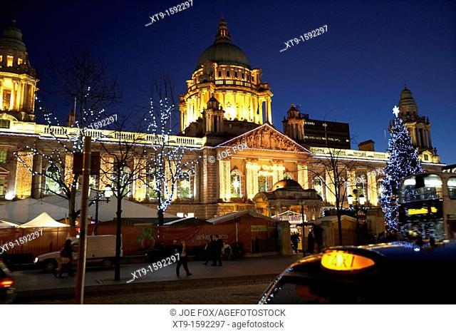 taxi outside belfast city hall illuminated with christmas lights and xmas market northern ireland uk