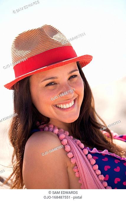 Smiling woman wearing sun hat on beach