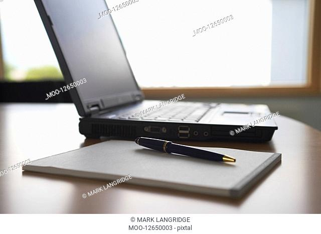 Laptop and notepad on desk