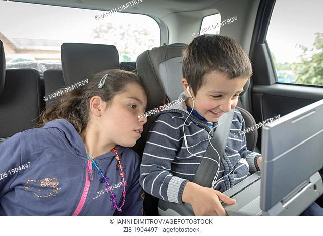 Children watching a movie on the backseat of a car