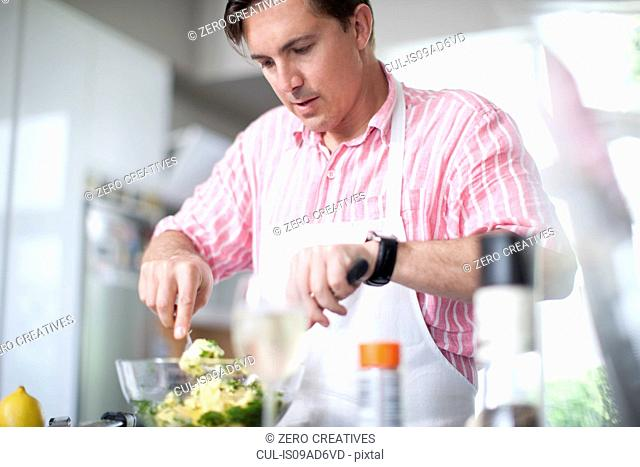 Mature men cooking, mixing ingredients in bowl
