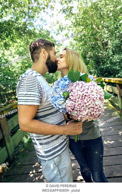Couple with with a bouquet of hydrangeas kissing on a wooden walkway in the countryside