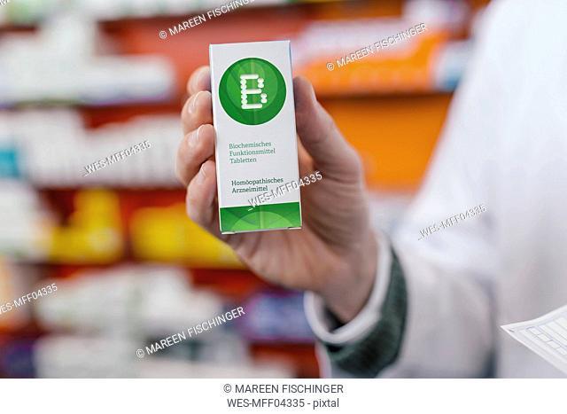Pharmacist holding homeopathic medicine in pharmacy