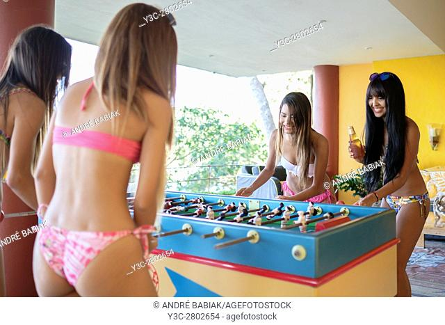 Young women enjoying a game of table football on an outdoor terrace in Mexico
