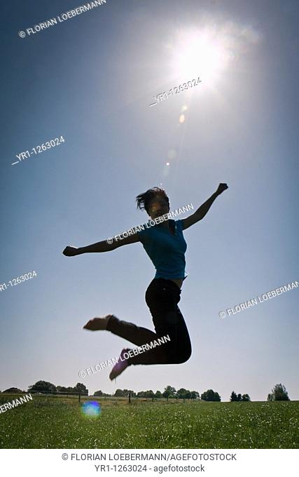 Asian girl jumping in a field during summer. Shot in Aachen, Germany