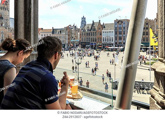 Bruges, Belgium - July 7, 2017: Tourists drinking beer and eating chocolate while enjoying the a panoramic view of the market square in the center of Bruges