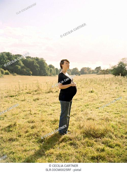 Pregnant woman standing in field