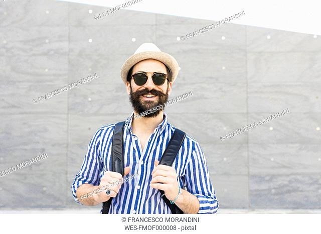 Portrait of bearded young man with sunglasses, hat and backpack