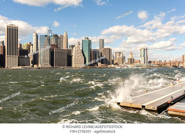 The windy, choppy waters of the East River break against a breakwater in Brooklyn Bridge Park in New York