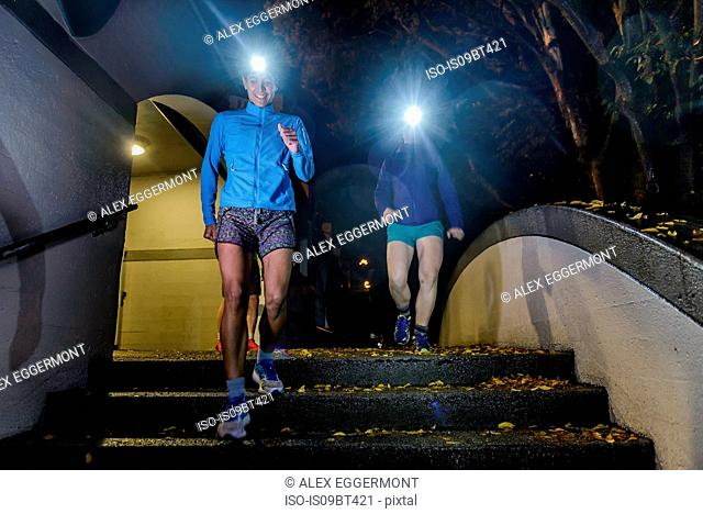 Runner with headlamp going down stairs, North Vancouver, Canada