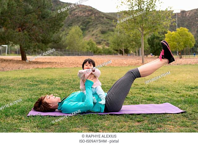 Mother exercising with baby in park