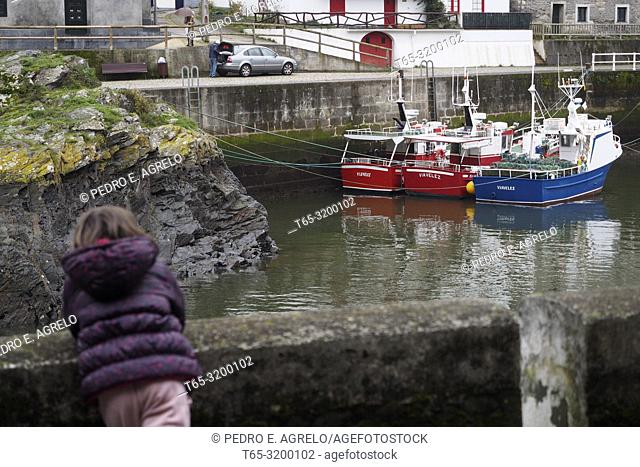 A little girl looks at the fishing boats in the small fishing port in Viavélez, Asturias. Cantabrian Sea