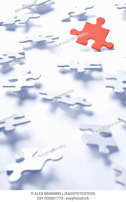 Jigsaw puzzle pieces on a white background with one red piece