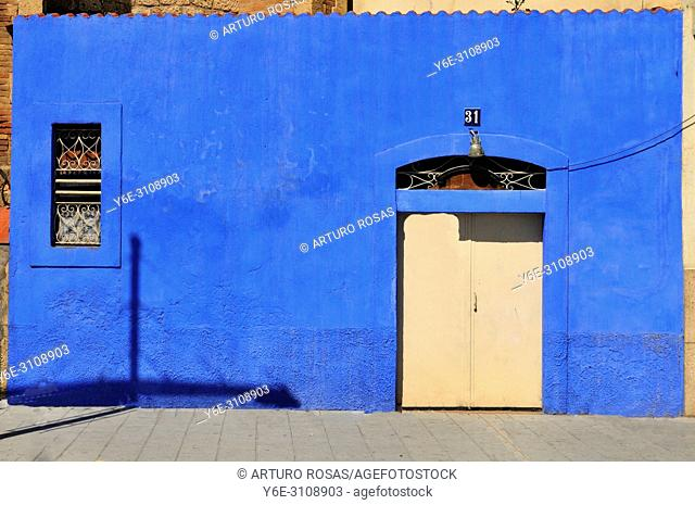 Door in a blue wall in the port district of Tarragona, Catalonia. Spain