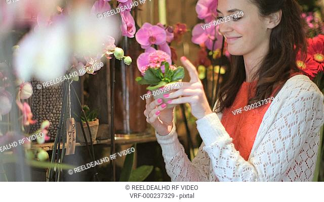 A young woman reaches out smells the flowers in their array