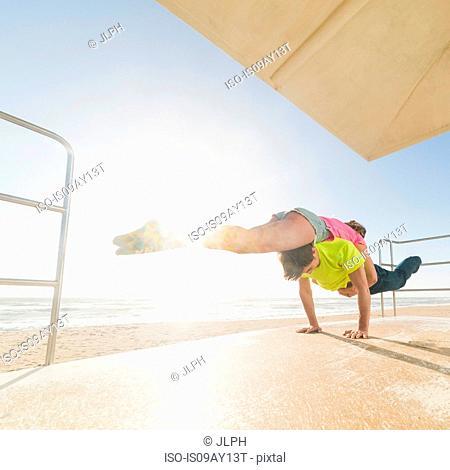 Couple practising partner yoga on beach lifeguard tower