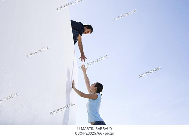 A man helping a woman climb a wall