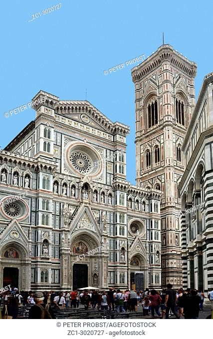 Tourists on the Piazza del duomo in front of the Cathedral of Santa Maria del Fiore with Giottos campanile in Florence - Italy