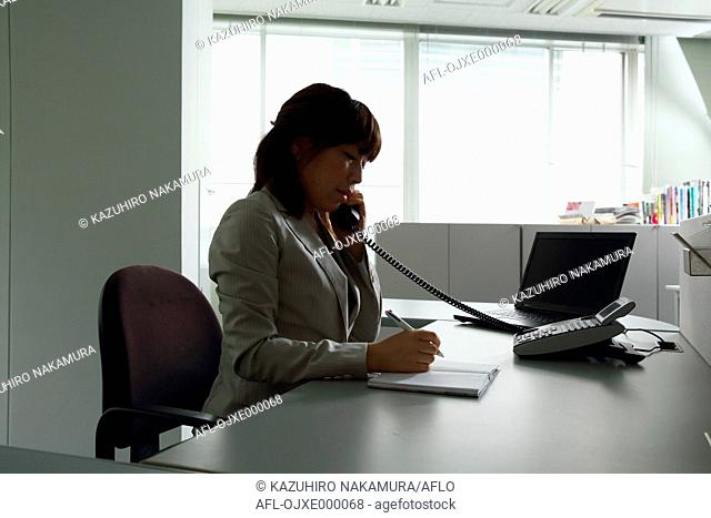 Young Japanese business woman working at her desk