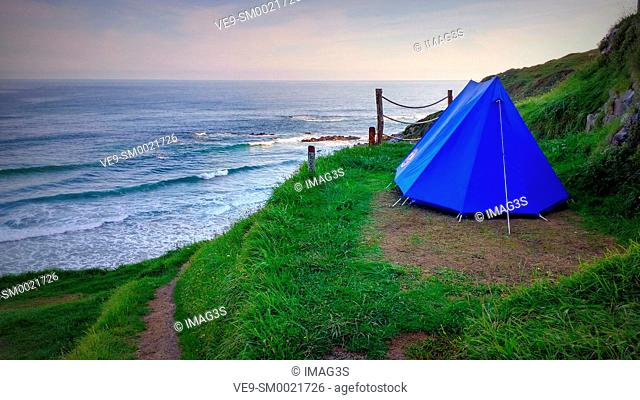 A tent pitched on a coastline next to cliffs at dawn, Camping La Paz, Vidiago. Llanes municipality. Asturias, Spain