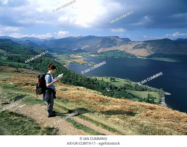 Walker reading map and looking past Derwent Water and up Borrow Dale as seen from Blueberry Fell