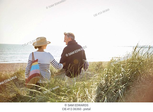 Mature couple walking arm in arm on sunny beach