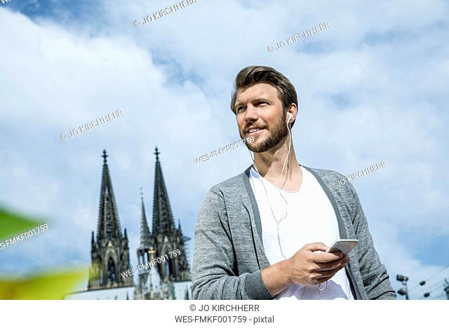 Germany, Cologne, portrait of young man with smartphone hearing music